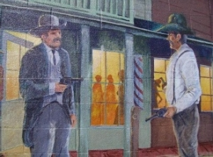 """""""A Dangerous Arrest"""" by Richard Perkins, John Knowlton, Kathy Sexton, Jenna Morgenstein, MaryGipson-Knowlton, 2000. This mural shows an """"Old West"""" event that broke the peace and quiet of  Bishop on March 10, 1887. Philip Staiger was reported to be drunk and disorderly, threatening a abystander with a gun and resisting arrest. 207 West Line Street, Bishop Police Station . 11.5' x 15'"""