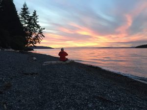 Pam admiring the sunset while kayak-camping